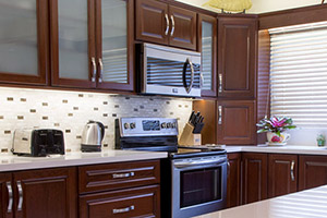 Appamat Balandra Kitchen in General Finishes Brown Mahogany Stain and paired with Stainless Steel Pulls